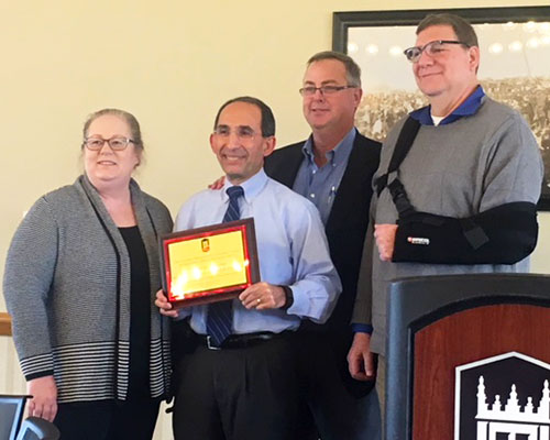 Terry Borg accepts a plaque from NIU Graduate School Dean Brad Bond (back) while Office of External and Global Programs colleagues Gail Hayenga (left) and Ted Moen (right) share in the honor.