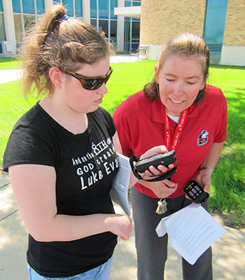 Stacy Kelly (right) looks at a student's Victor Reader Trek.