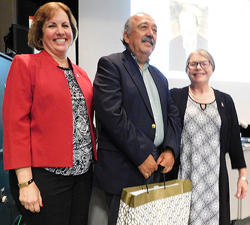 Dean Laurie Elish-Piper and Suzanne Degges-White, chair of the Department of Counseling, Adult and Higher Education, recognize Jorge Jeria, who is retiring.