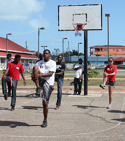 Jacobs (right) stretches during a Belizean Youth Sport Coalition visit.