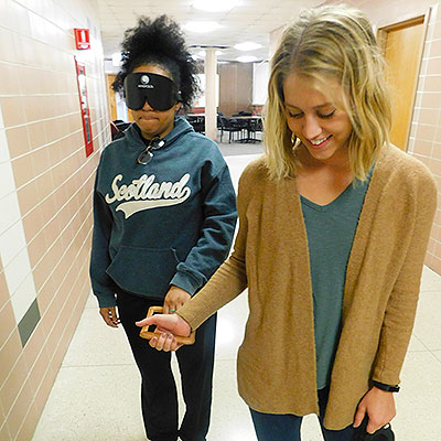 NIU students learn about training the use of seeing-eye dogs by playing the role of the person who is blind or visually impaired – and the dog.