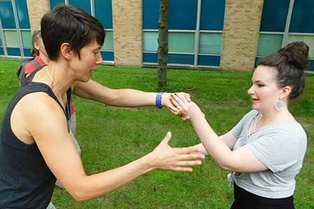 Adventure Therapy Best Practices workshop participants designed and practiced secret handshakes outside Gabel Hall.