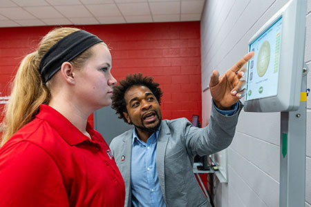 Emerson Sebastião, an assistant professor in the Department of Kinesiology and Physical Education, demonstrates some of the new technology with kinesiology major Becca Backeberg, president of the Exercise Science Club.