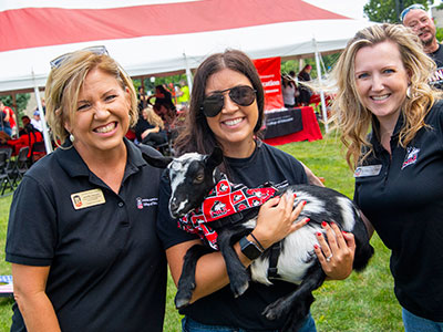 Jennifer Johnson (left), director of teacher preparation for the NIU College of Education, Brittany Wereminski and Christine Schweitzer (right), Elementary Education advisor in the Department of Curriculum and Instruction, meet David Walker's goat, XXX, at the New Student Welcome Picnic.