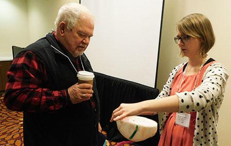 Elizabeth Hipskind explains her Styrofoam eyeball model to William Penrod.