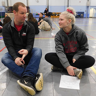 Geneva High School P.E. teacher Scott Hennig talks with NIU student Madison Mikos.